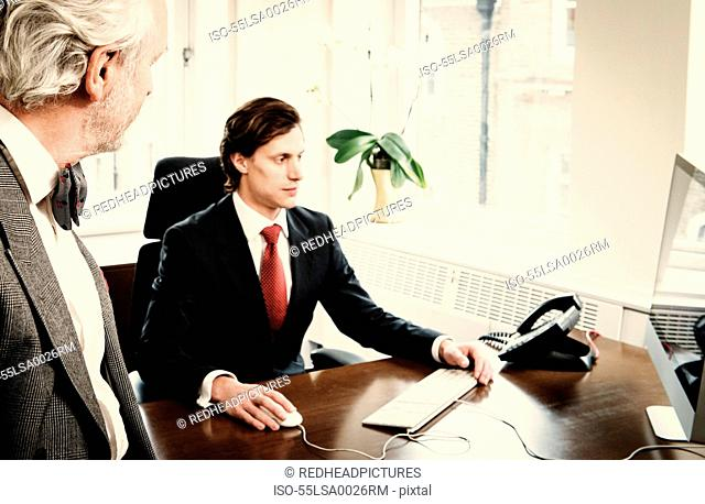 Young businessman at desk with senior man in office