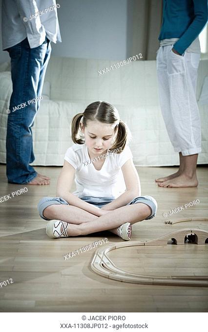 Sad little girl sitting on floor