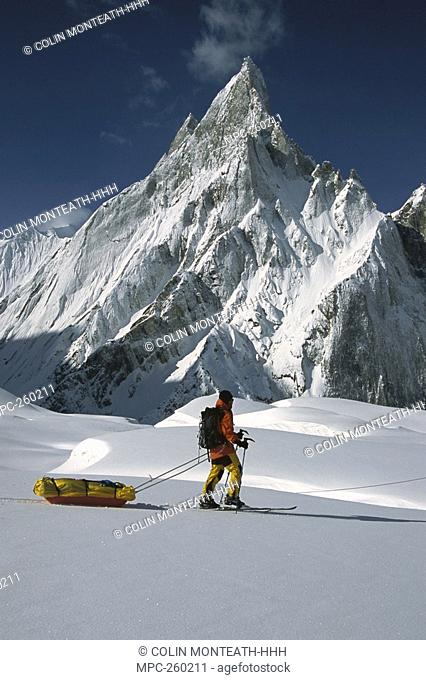 Skier passing icy Mitre Peak, Baltoro Glacier, Karakoram Mountains, Pakistan