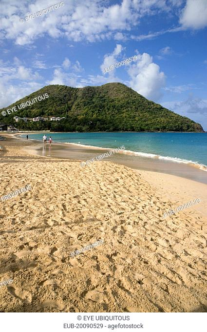 Reduit Beach in Rodney Bay during the early morning with tourists walking by the waterline