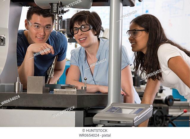 Graduate assistant explaining the coordinate measuring machine