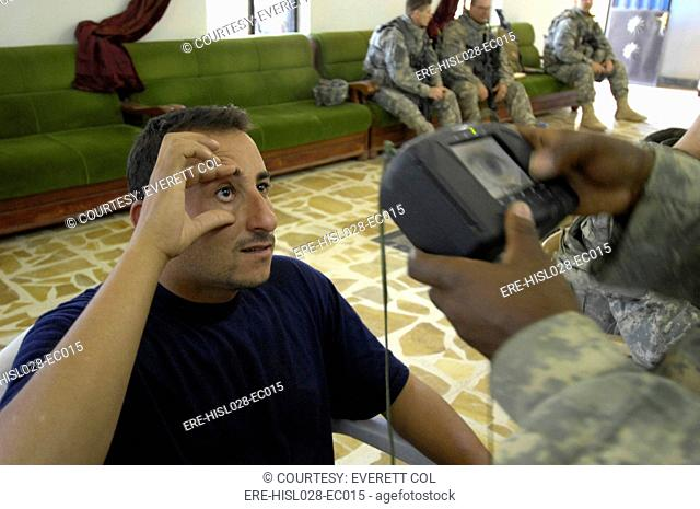 An Iraqi candidate for the Sons of Iraq security force holds his eye open for a retinal scan administered by a US Soldier in Wasit Province Iraq