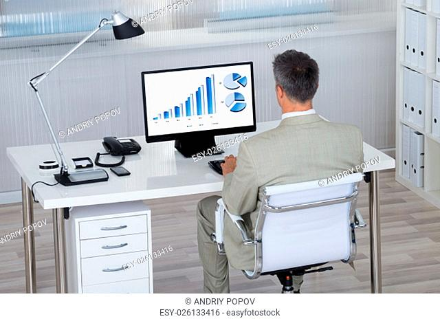 Rear view of businessman analyzing financial graphs on computer at desk in office