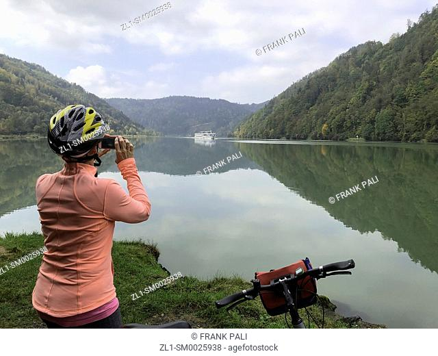 Tourist taking photo fo cruiseship along the Danube river Germany