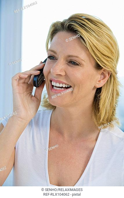 Mature woman smiling while using Cell phone, portrait
