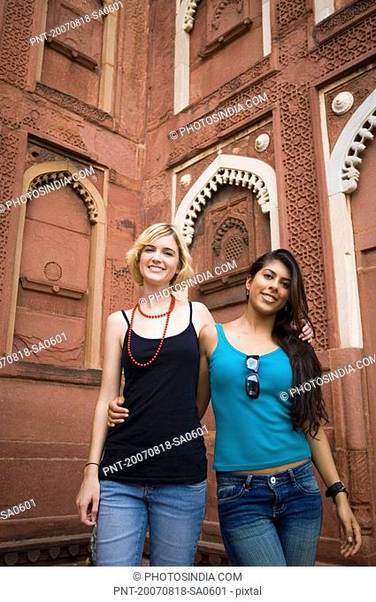 Portrait of two young women standing together and smiling, Taj Mahal, Agra, Uttar Pradesh, India