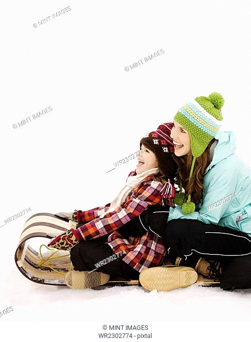 Two children sitting on a sledge on the snow
