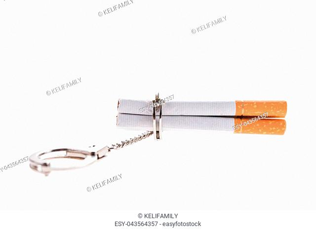 Addition concept with cigarettes and handcuffs on white background