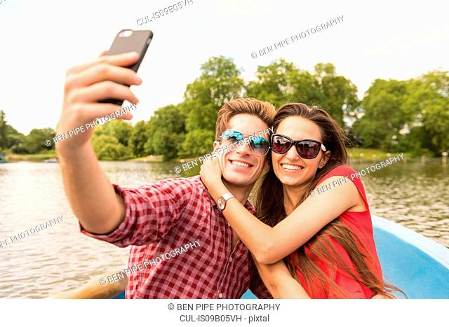 Young couple taking smartphone selfie in rowing boat in Regents Park, London, UK