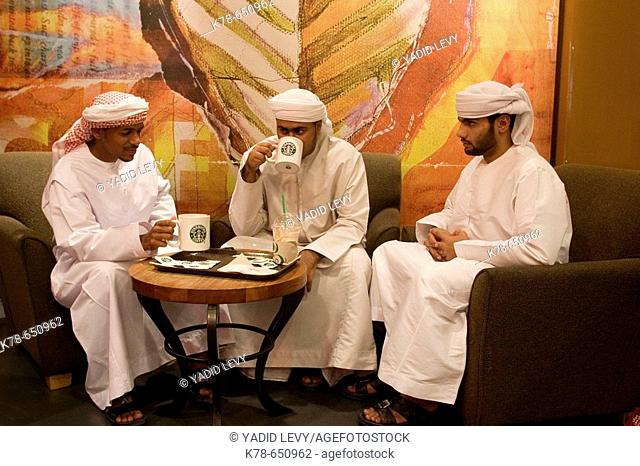 Young arab men with traditional dress sitting at starbucks cafe in Deira city centre shopping mall. Dubai, United Arab Emirates