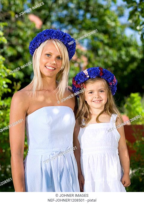 Mother and daughter standing in garden, portrait, close-up