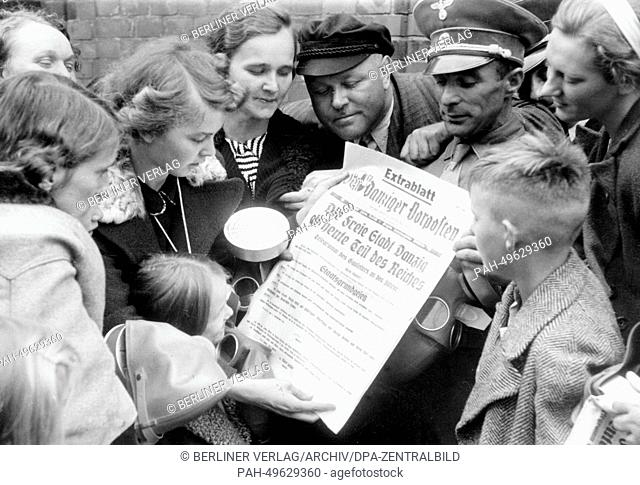 "The Nazi propaganda photo shows men, women and children reading an extra page in the Nazi newspaper """"Danziger Vorposten"""" entitled """"The Free City of Danzig is..."
