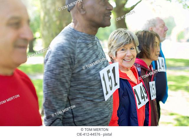 Portrait active senior woman at sports race starting line in park