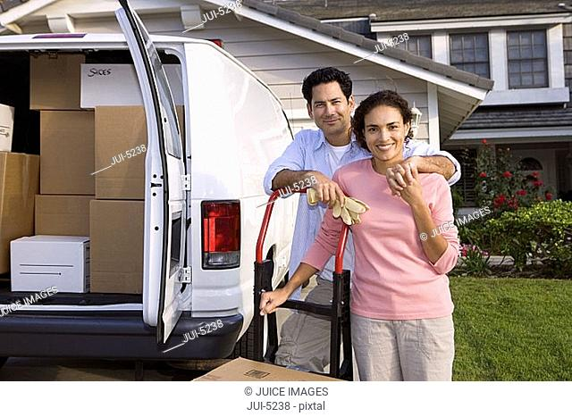 Couple moving house, standing beside van in driveway, leaning on hand dolly, smiling, portrait