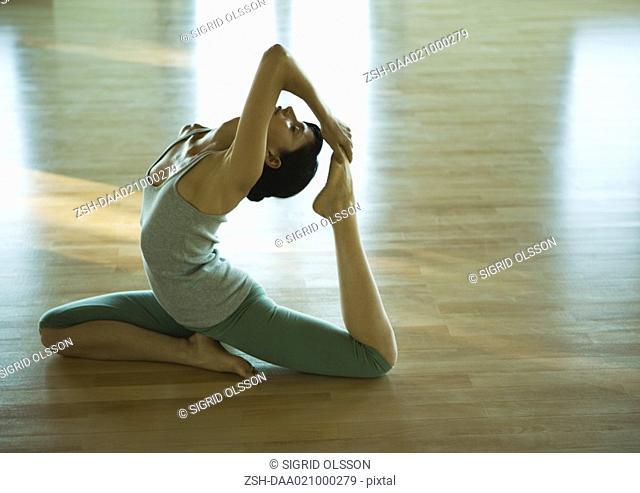 Woman doing one-legged king pigeon pose