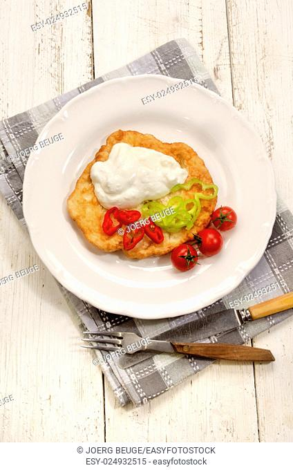 rustic hungarian breakfast with langos, sour cream and sliced chili on a plate