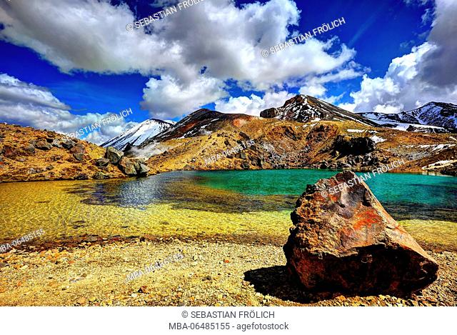 Volcanic stone lump in crystal clear Emerald Lake in the Tongariro national park, in the background of the Red Crater of the Mt. Ngauruhoe