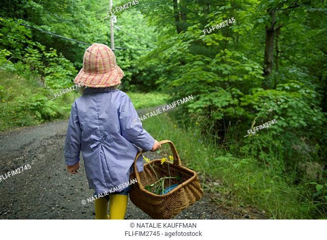 Little Girl in a Rain Coat and Rubber Boots with a Basket Walking down a Trail, Lake Muskoka, Bracebridge, Ontario