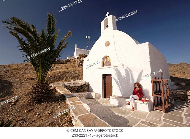 Woman sitting in front of a chapel at the top of the hill in Chora, Ios, Cyclades Islands, Greek Islands, Greece, Europe