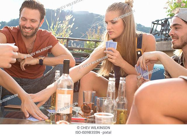 Adult friends playing cards at roof terrace party