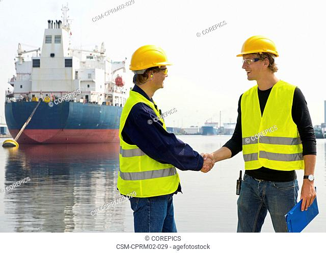 Two dockers meeting at an industrial harbor, in front of a large oil tanker