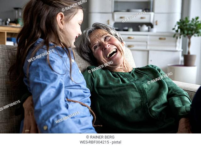 Laughing grandmother and her granddaughter on the couch at home