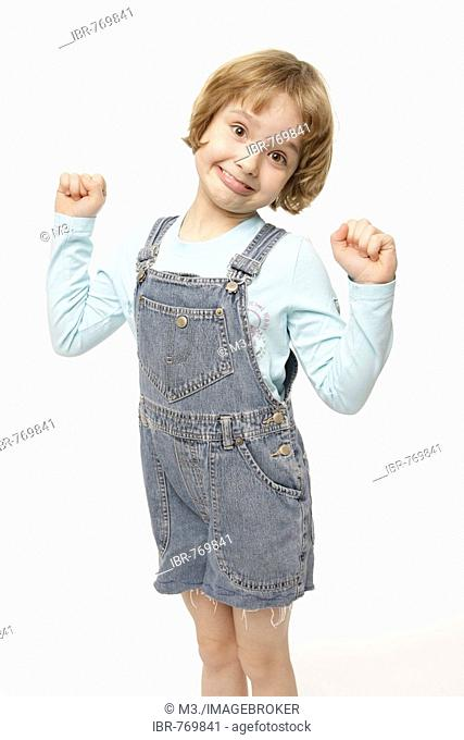 Dark-blonde, 8-year-old girl acting goofy, winner's pose