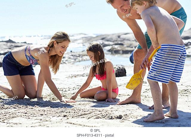 MODEL RELEASED. Family playing on the beach with bucket and spade