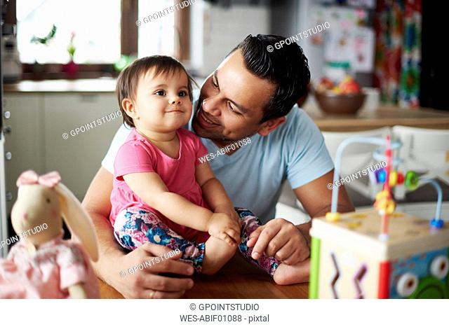 Smiling father with baby girl at home