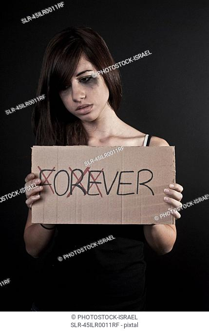 Crying teenage girl holding over sign
