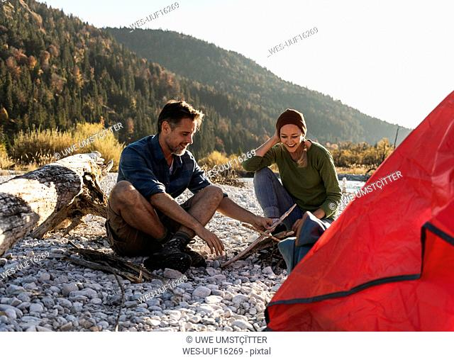 Mature couple camping at riverside with wood for a camp fire