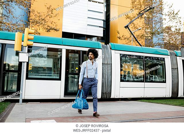 Spain, Barcelona, man with bag crossing the street in front of a tramway