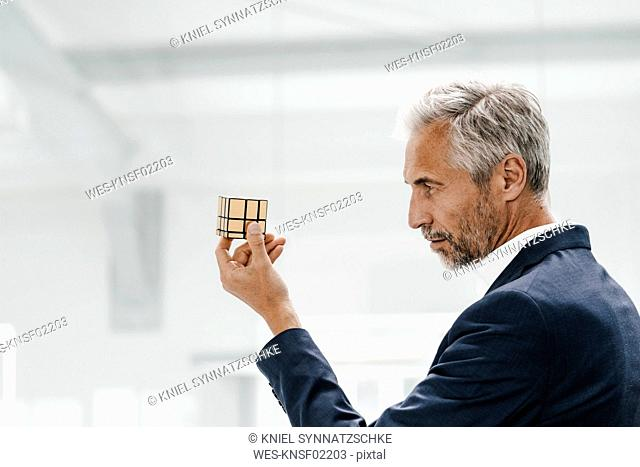 Mature businessman in office examining Rubik's Cube
