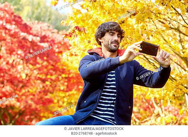 Selfie, Man in the forest making a photo with smartphone, Trees in Autumn, Pagoetako Parke Naturala, Pagoeta Natural Park, Aya, Gipuzkoa, Basque Country, Spain