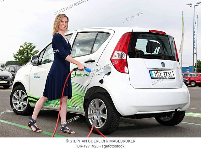 Woman inserting the charging plut into the socket of a Suzuki Splash electric car, Fuerth, Bavaria, Germany, Europe