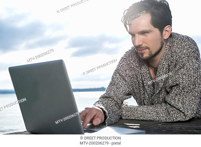 Close up portrait man using laptop outside