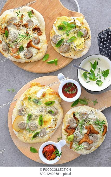 Mini pizzas with mushrooms pear basil white sausage served with tomato sauce