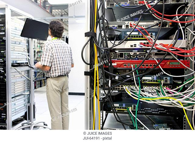 Technician working on computer in Server room of data center