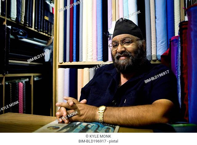 Indian business owner sitting in fabric store