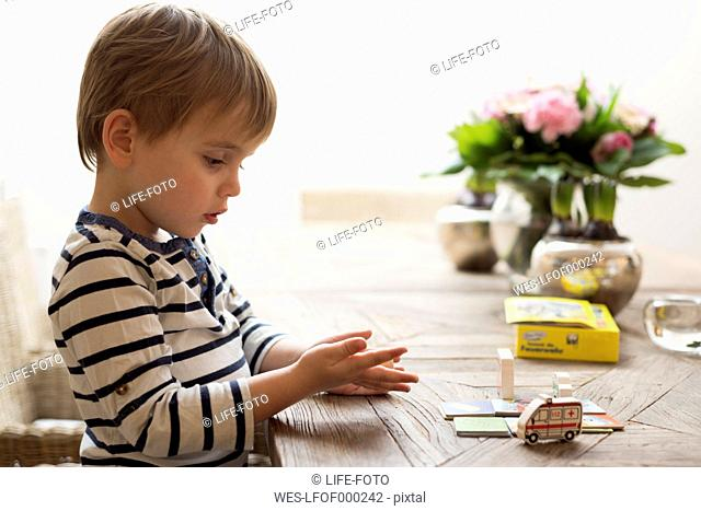 Little boy playing at dining table