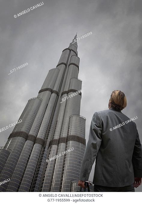 Businessman under high rise building, Dubai, UAE