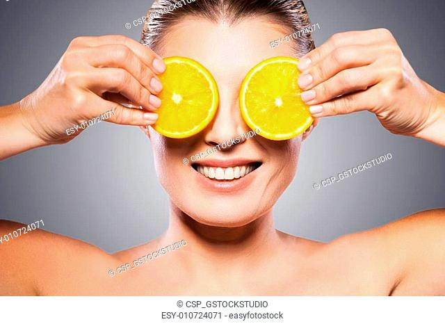 Only natural ingredients. Cheerful mature woman holding pieces of orange in front of her eyes while standing isolated on white background