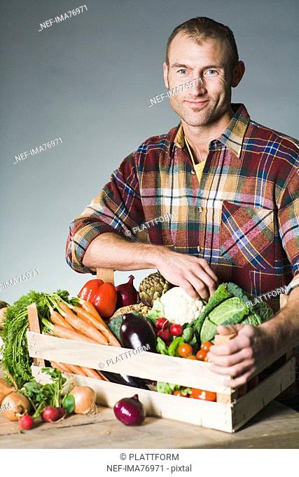 Man holding a box of vegetables