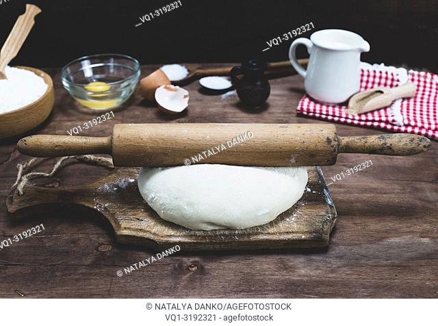 piece of white wheat flour dough on a brown board and a wooden rolling pin, vintage toning
