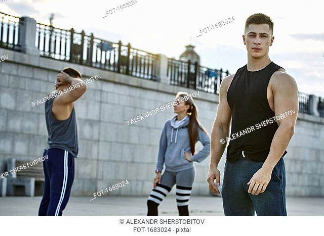 Portrait of confident young athlete standing with friends against bridge