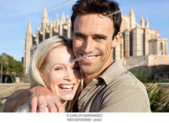 Spain, Mallorca, Palma, Couple hugging with St Maria Cathedral in background, smiling, portrait