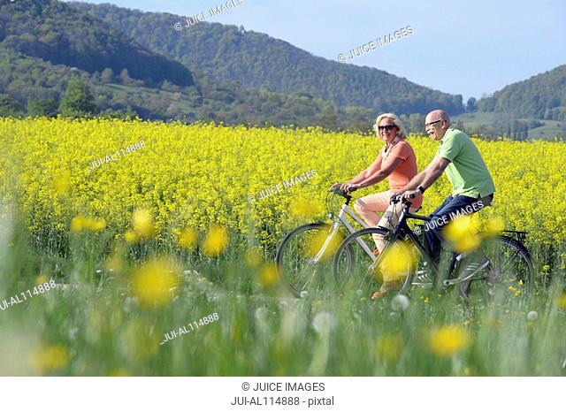 Couple riding bicycle by field in countryside