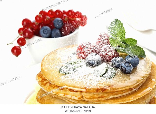 Pile of delicious handmade pancakes topped with honey, raspberries and blueberries