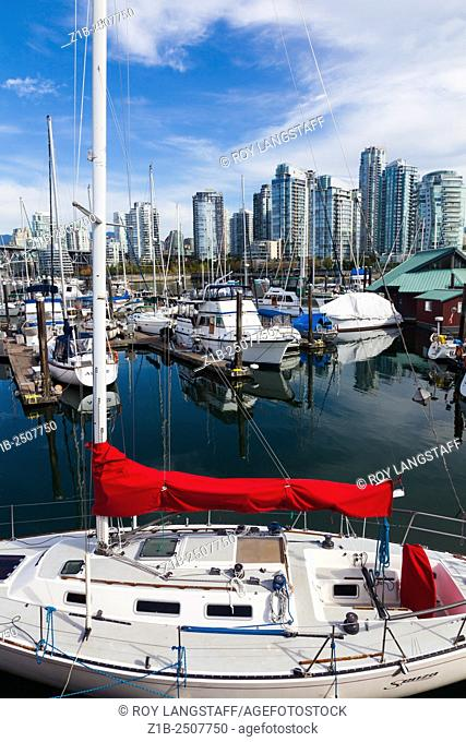 Small yacht with a vibrant red sail cover in a marina on False Creek, Vancouver