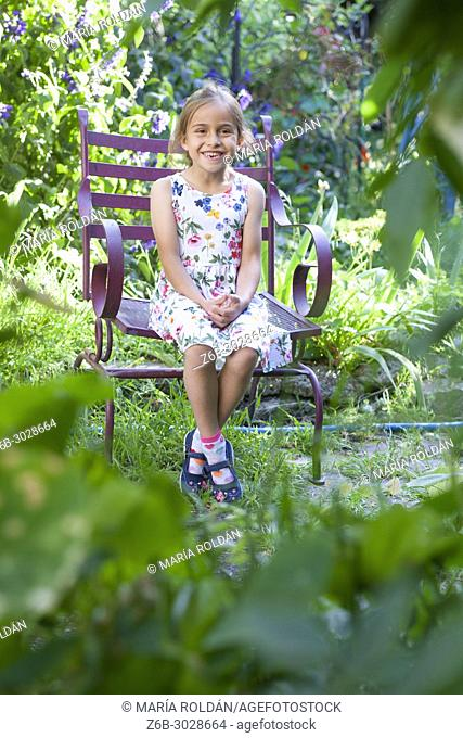 happy little girl sitting on a chair in lush garden